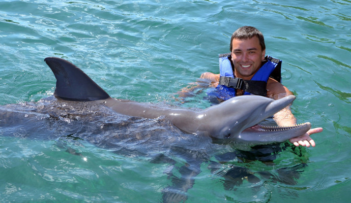 Happy man swim with dolphin